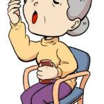 薬を飲む高齢女性